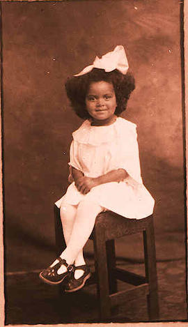 Portrait of a young girl sitting on a stool.