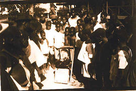 African villagers gathered around a record player.