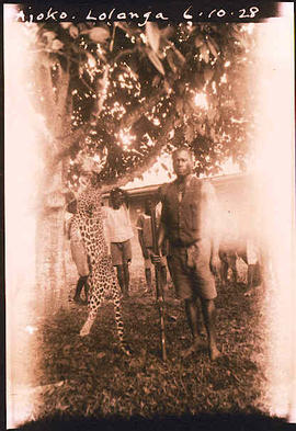 A hunter (Ajoko Lolanga) and his kill, a leopard.