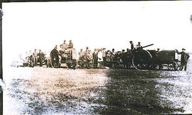 A group of people standing besides tractors.