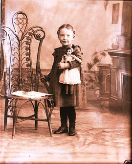 Portrait of a young girl holding a doll.