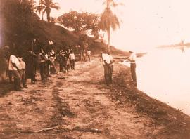 A crowd of Africans near a river bank.