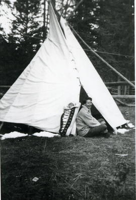 Woman & baby in papoose carrier in front of teepee.