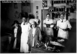 Butchers with customers in butcher shop in Blairmore, Alberta.