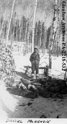 Daniel McKenzie beside woodpile, Stanley Mission, Saskatchewan.