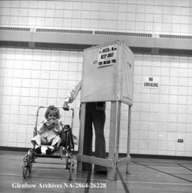 A little girl awaits her mother who is voting in civic elections, Calgary, Alberta.