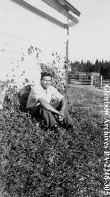 James Brady sitting outdoors, Cumberland House, Saskatchewan.