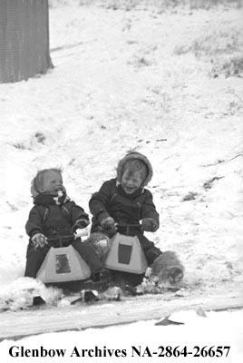 Two children play in the snow on toy snowmobiles, Calgary, Alberta.