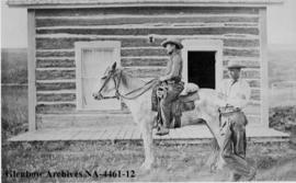 Two cowboys beside log house, Cochrane Ranche, Alberta.
