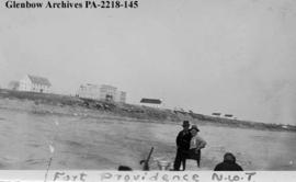Roy Erickson and Frank Chaisson stand in foreground, Fort Providence, Northwest Territories.