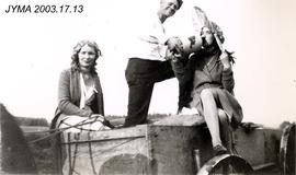 A group of three in a horse drawn wagon