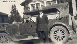 Bob Findlay posing with automobile in front of the Findlay residence