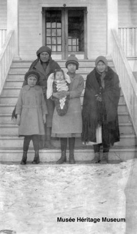 Women and girls with baby in a papoose at 3rd residential school at Onion Lake, Saskatchewan