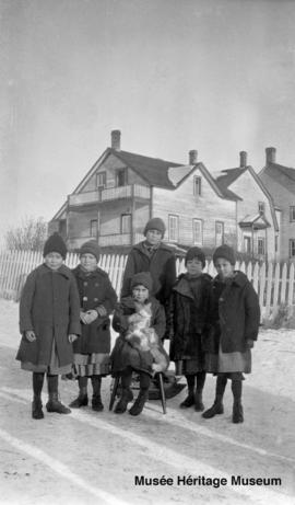 Girls, one with cat, in front of 2nd residential school at Onion Lake, Saskatchewan
