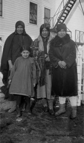 Women and a girl in front of 3rd residential school at Onion Lake, Saskatchewan