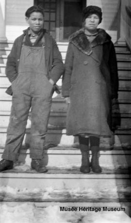 Boy and girl in front of 3rd residential school at Onion Lake, Saskatchewan