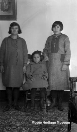 Three girls inside building at Onion Lake, Saskatchewan