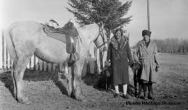 Two individuals and a horse standing near the old mission at Onion Lake, Saskatchewan