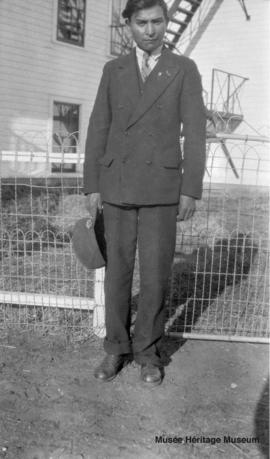 Man in front of 3rd residential school at Onion Lake, Saskatchewan