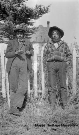 Jim Cannepotato and Charlie Chief standing in front of the old mission at Onion Lake, Saskatchewan