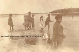 First Nations children playing with a toy sailboat at the waters edge in the Lake of the Woods, O...