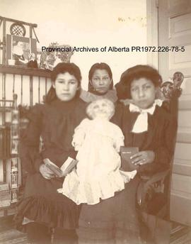 Portrait of three First Nations girls with a doll in the Lake of the Woods, Ontario area