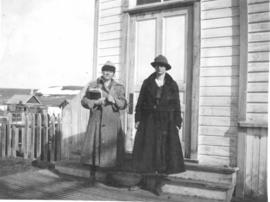 2 young women on front steps of a building, Okotoks, AB.