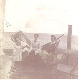Three women and a child sitting on a hammock, ranch at Blackie, AB.