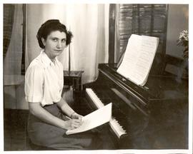 Violet Archer composing music with a piano.