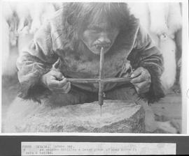 Canada. Hudson Bay. An Esquimo drilling a large piece of soap stone to make a kettle / 38880