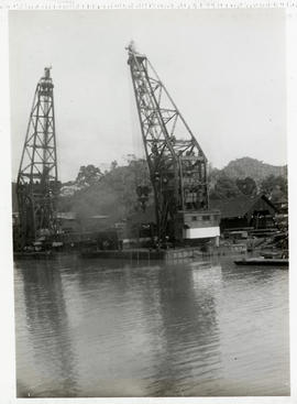 [Two cranes in boatyard on water]
