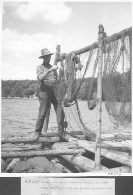 An old Nova Scotia fisherman mending his nets while they dry in the sun on Nova Scotia's South sh...
