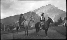 [Unidentified man and woman on horses, posing on Banff Avenue]