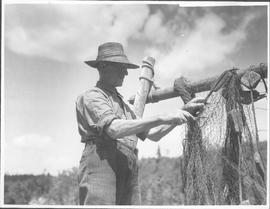 Canada (Nova Scotia). Close-up of an old fisherman on Nova Scotia's South Shore shown mending a n...