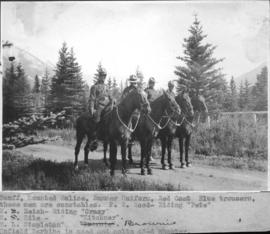 "Banff, mounted police, summer uniform, red coat, blue trousers. These men are constables: F. W. Wood, riding ""Pete""; W. Neish, riding ""Crazy""; W. Hile, riding ""Kitchner""; E. L. Stapleton, riding ""Brownie"". Enfield Carbine is used and colts 45-6 shooter / 27689"