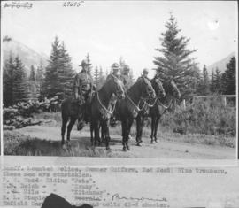 "Banff, mounted police, summer uniform, red coat, blue trousers. These men are constables: F. W. Wood, riding ""Pete""; W. Neish, riding ""Crazy""; W. Hile, riding ""Kitchner""; E. L. Stapleton, riding ""Brownie"". Enfield Carbine is used and colts 45-6 shooter / 27695"