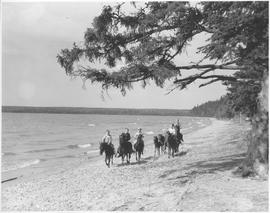 Canada. Manitoba Riding Mt. National Park. Children riding ponies along the shore of Clear Lake / CN209